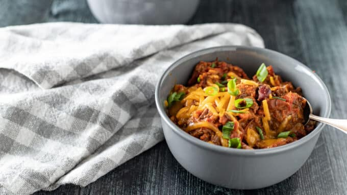 Heaping bowl of chili with toppings.